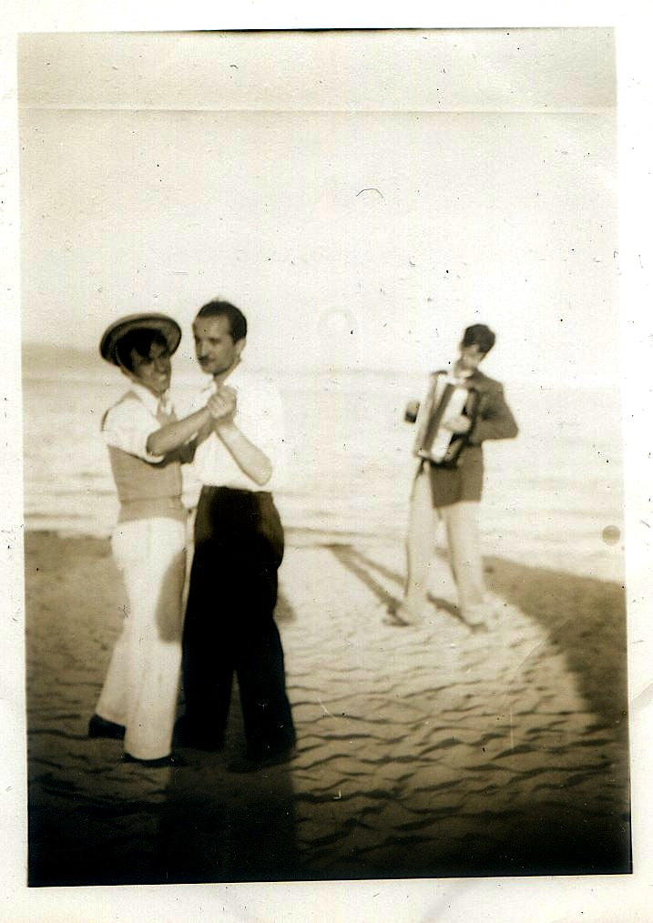 Men dancing with each other on a beach with accordion player